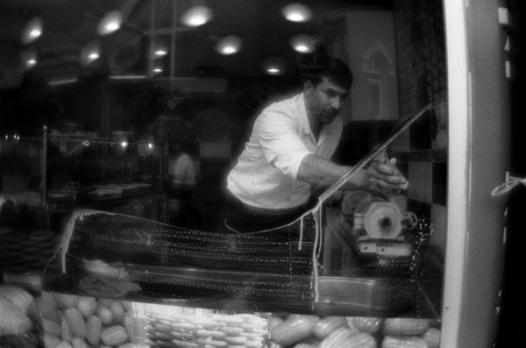 Man cleans the window of confectioner's shop. Fener district, Is